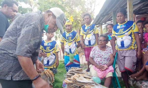 Cabup Supiori, Drs. Yan Imbab ketika membeli ikan asin di mama-mama penjual asal Supiori di Kampung Insumbabi, pada Selasa (24/11/2020). Kedepan pengembangan ikan asin bakal dilakukan oleh para pemuda setempat selain mama-mama penjual asal Supiori