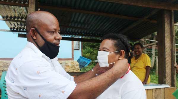 Cawabup Nomor Urut 5, Nichodemus Ronsumbre ketika memakaikan masker kepada salah seorang pendukung IMANI di Kampung Yawerma, Supiori Timur, beberapa waktu lalu