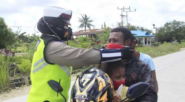 Salah satu anggota Satgas Aman Nusa II Matoa saat memakaikan masker kepada pengendara roda dua