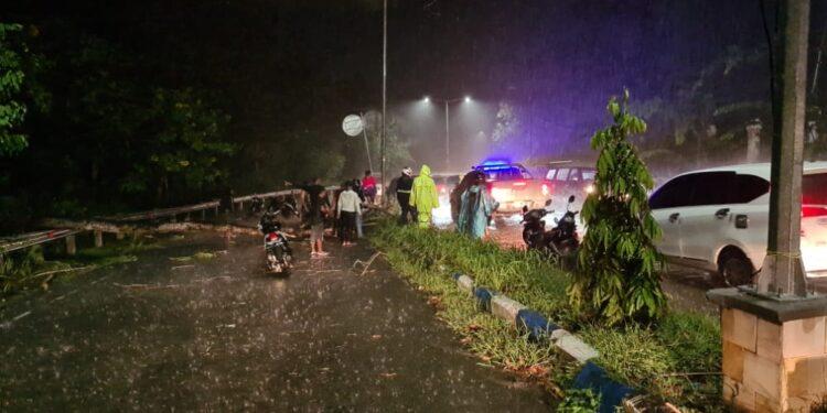 Personil Lantas Polres Jayapura Membersihkan Pohon Tumbang di Kompleks Kantor Pemerintah Kabupaten Jayapura Karena Curah hujan Tinggi, Rabu (3/2/2021)