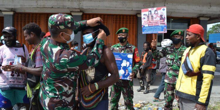 Personel Kodim 1710/Mimika Bagikan Masker Gratis Kepada Masyarakat Timika, Minggu (7/2/2021)