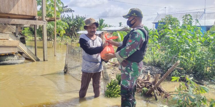Satgas Pamtas RI-PNG Yonif Mekanis Raider 413 Kostrad Serahkan Bantuan kepada warga terdampak banjir di Kampung Yowong, Distrik Arso Barat, Kabupaten Keerom, Minggu (8/2/2021)