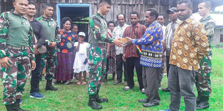 Personel Satgas Pamtas Yonif Raider 100/PS Pos Kotis Membagikan Alkitab kepada Masyarakat i Kampung Wonorejo, Distrik Mannem, Kabupaten Keerom, Provinsi Papua. Minggu, (7/2/2021).