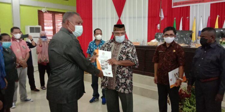 Ketua KPU Teluk Bintuni Herry Arius E. Salamahu menyerahkan SK Penetapan Bupati dan Wakil Bupati Teluk Bintuni terpilih kepada Wakil Bupati Matret Kokop,S.H di Aula KPU Teluk Bintuni, Sabtu (20/2/2021). (Foto : Ist)
