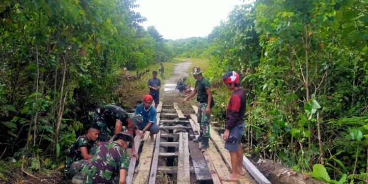 Prajurit Satgas Pamtas RI-PNG 312/KH Bersama Warga Perbaiki Jembatan di Kampung Towe Hitam, Distrik Towe, Kabupaten Keerom, Papua, Sabtu (20/2/2021). Foto: Pendam Cenderawasih