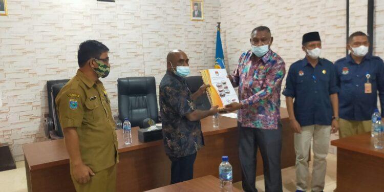 Ketua KPU Teluk Bintuni Herry Arius E Salamahu meneyrahkan dokumen penetapan Bupati dan Wakil Bupati Teluk Bintuni kepada Ketua DPRD Teluk Bintuni di Gedung DPRD Teluk Bintuni, Selasa (23/2/2021).(Foto : Ist)