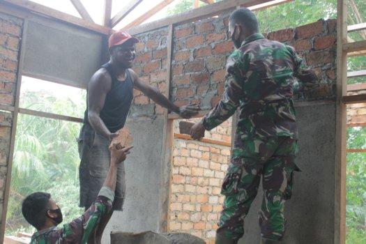 Personel Satgas Pamtas RI-PNG Yonif 611/Awang Long Pos Kalimaro bantu membangun rumah warga Kampung Bupul, Distrik Eligobel, Kabupaten Merauke, Papua, Selasa (23/2/2021). Foto: Pendam Cenderawasih