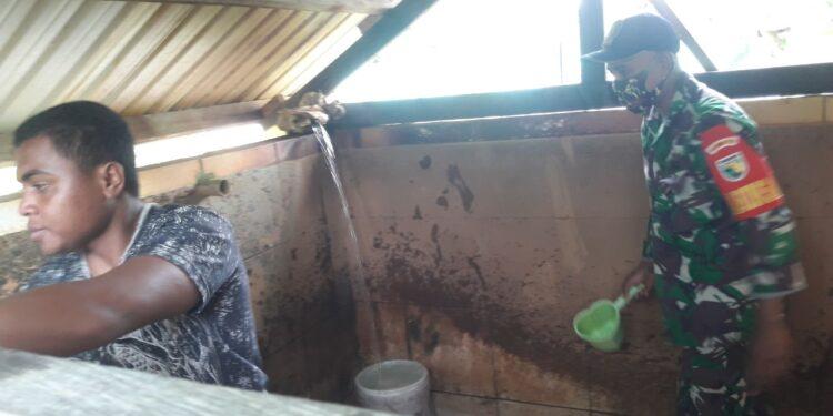 Babinsa Koramil 1710-07/Mapurujaya, Serda Imam Nawawi, membantu warga binaan bersihkan bak penampungan air bersih di kampung Hiripau, Distrik Mimika Timur, Kabupaten Mimika, Senin (1/03/2021). Foto: Pendam Cenderawasih