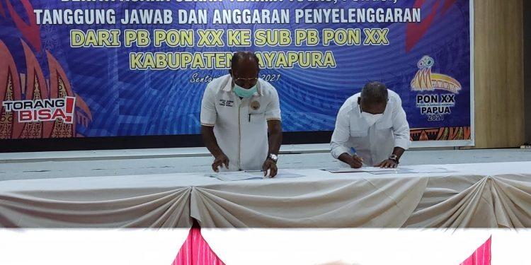 Ketua Harian PB PON XX, DR. Yunus Wonda dan Ketua Sub PB PON XX Klaster Kabupaten Jayapura, Mathius Awoitauw, menandatangani berita acara pergeseran anggaran PON Papua di Hotel Suni Garden Sentani, Rabu (16/6/2021) / Foto: IDI