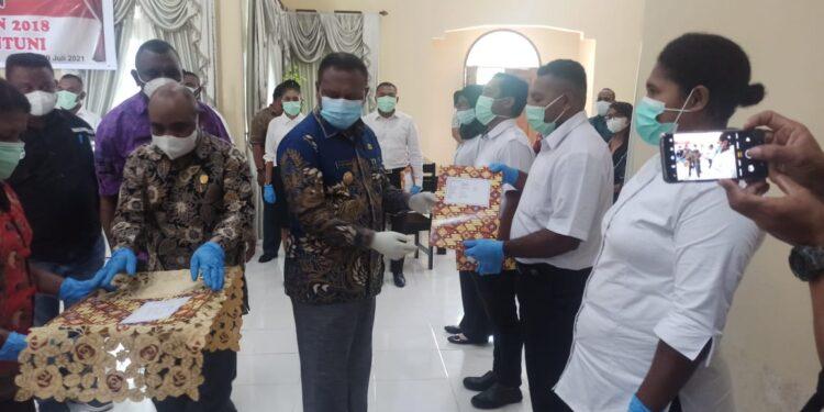 Bupati Teluk Bintuni Ir Petrus Kasihiw,M.T menyerahkan SK CPNS Farmasi 2018 kepada 8 orang perwakilan di Rumah Tamu Negara Kabupaten Teluk Bintuni, Jumat (9/7/2021).(Foto : Istimewa)