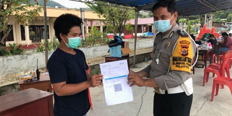 Personil Bhabinkamtibmas Polsek Jayapura Selatan serahakn surat vaksin kepada salah satu warga yang telah vaksin di lapangan PTC Entrop, Kota Jayapura, Minggu (19/9/2021) / Foto: Humas Polda Papua