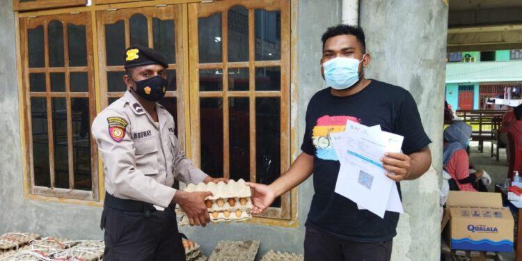 Personil Polresta Jayapura Kota serahkan bingkisan telur ayam kepada warga yang sudah vaksin di GPDI Marantha Abepura, Minggu (19/9/2021) / Foto: Humas Polda Papua